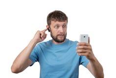 Cuffia avricolare d'uso e smartphone dell'uomo barbuto Fotografia Stock