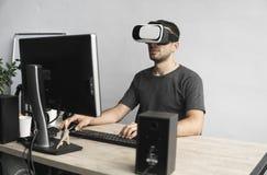 Cuffia avricolare degli occhiali di protezione di realtà virtuale del giovane, scatola del vr e seduta d'uso nell'ufficio contro  immagini stock libere da diritti