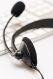 Cuffia avricolare dell'ufficio con la tastiera del microfono sullo scrittorio immagine stock libera da diritti