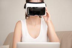 Cuffia avricolare di VR per il computer portatile, vetro d'uso di realtà virtuale della giovane donna Fotografie Stock Libere da Diritti