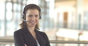 Cuffia avricolare sorridente della donna del receptionist dell'operatore di sostegno di servizio di assistenza al cliente di call stock footage