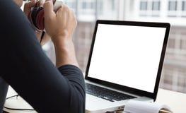 cuffia startup della tenuta dell'uomo con il computer portatile mentre sedendosi il legno Immagine Stock Libera da Diritti