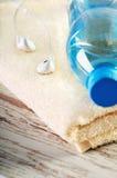 Cuffie bianche e una bottiglia del primo piano dell'acqua su una spugna Immagini Stock