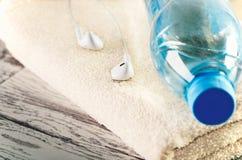 Cuffie bianche tinte di immagine e una bottiglia del primo piano dell'acqua sopra Fotografie Stock Libere da Diritti