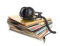Cuffie d'annata sulla pila di annotazioni di vinile Fotografia Stock