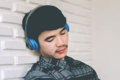 Cuffie d'ascolto di musica del giovane omosessuale dei pantaloni a vita bassa Fotografie Stock