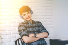Cuffie d'ascolto di musica del giovane omosessuale dei pantaloni a vita bassa Fotografia Stock Libera da Diritti