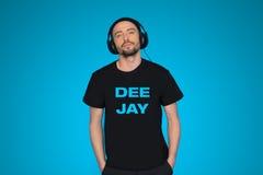 Cuffie d'uso del DJ dell'uomo sul blu Immagine Stock
