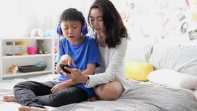 Cuffie d'uso del figlio e della madre facendo uso dello smartphone per il canto della canzone insieme a casa video d archivio