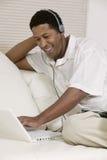 Cuffie d'uso dell'uomo che ascoltano la musica sul computer portatile Fotografie Stock Libere da Diritti
