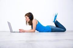 Cuffie d'uso della donna che si trovano sul pavimento con il computer portatile Fotografia Stock Libera da Diritti