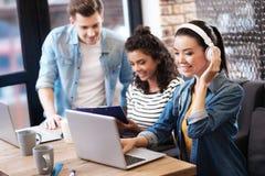Cuffie d'uso della ragazza felice e lavorare al computer portatile Immagini Stock