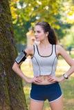 Cuffie d'uso e bracciale del corridore femminile Fotografia Stock