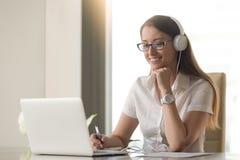 Cuffie d'uso sorridenti della giovane donna di affari che esaminano il rivestimento del pc Immagini Stock