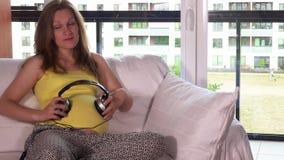 Cuffie della tenuta della donna incinta sulla pancia ed ascoltare la musica in salone archivi video