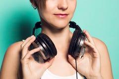 Cuffie di musica su un collo del ` s della ragazza Donna con i caschi di musica fotografie stock libere da diritti