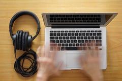 Cuffie e computer portatile per il lavoro moderno Immagine Stock
