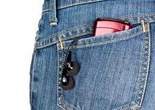 Cuffie e giocatore nella casella posteriore dei jeans Immagine Stock