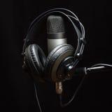 Cuffie e microfono a condensatore sui precedenti scuri Immagine Stock