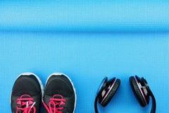 Cuffie e scarpe di sport sul fondo della stuoia di yoga Immagini Stock