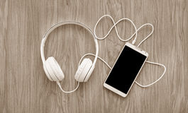 Cuffie e smartphone su di legno Immagini Stock