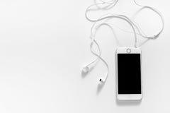 Cuffie e telefono cellulare bianchi Immagini Stock Libere da Diritti