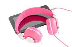 Cuffie femminili rosa vibranti e pc nero della compressa Fotografie Stock Libere da Diritti