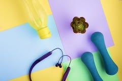 Cuffie moderne, teste di legno blu, bottiglia di acqua gialla sui blocchetti luminosi di colore Concetto di stile di vita nel mot immagine stock libera da diritti