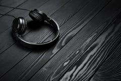 Cuffie nere su fondo scuro di legno nero Immagine Stock