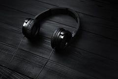 Cuffie nere su fondo scuro di legno nero Fotografie Stock