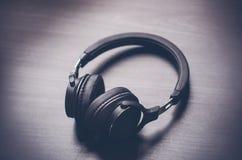 Cuffie su un fondo scuro Accessori di musica Cuffie di Bluetooth senza cavo fotografia stock