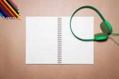 Cuffie, taccuino, penna e matite verdi di colore su una carta marrone Fotografie Stock