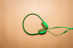 Cuffie verdi su un fondo della carta marrone Fotografia Stock