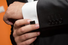 Cufflink. Groom pin his cufflink to the sleeve Stock Photos