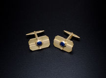 Cufflink. Yellow gold cufflink with sapphire, front view on black background royalty free stock photo