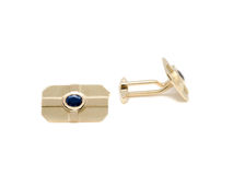Cufflink. Yellow gold cufflink with sapphire, front view on white background stock photos