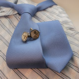 Cufflinks and blue tie on shirt Royalty Free Stock Images
