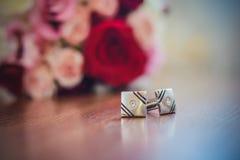 Cufflinks för muffar bredvid bröllopbuketten royaltyfria foton