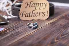Cufflinks and Father`s Day card. Belt near greeting paper. Prepare exclusive present for dad Royalty Free Stock Images