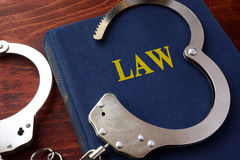 Cuffs and book with the Law. Cuffs and book with the title Law Royalty Free Stock Images
