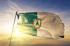 Cuiaba stad av tyg för torkduk för Brasilien flaggatextil som vinkar på den bästa soluppgångmistdimman arkivbild