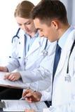 Cuida los papeles de escribir usando el tablero Médicos que discuten programa de la medicación o que estudian en la conferencia m fotografía de archivo libre de regalías