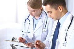 Cuida los papeles de escribir usando el tablero Médicos que discuten programa de la medicación o que estudian en la conferencia m foto de archivo libre de regalías