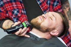 Cuidado de la barba hombre mientras que el recorte de su pelo facial cortó en la barbería foto de archivo libre de regalías
