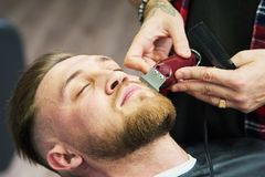 Cuidado de la barba hombre mientras que el recorte de su pelo facial cortó en la barbería fotos de archivo libres de regalías