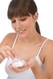 Cuidado de la carrocería - adolescente femenino que aplica la crema hidratante Foto de archivo