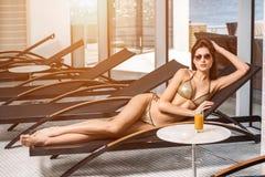 Cuidado de la carrocería Mujer con el cuerpo perfecto en el bikini que miente en el deckchair por la piscina imagen de archivo libre de regalías