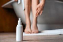 Cuidado de la carrocería Mujer joven en el cuarto de baño que frota ligeramente sus piernas Medios contra las varices y edema en  fotografía de archivo