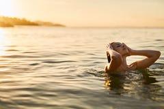 Cuidado de la carrocería Mujer que goza del mar, puesta del sol Forma de vida sana Verano Fotos de archivo