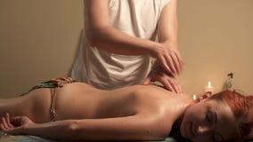 Cuidado de la carrocer?a Tratamiento del masaje del cuerpo del balneario Mujer que tiene masaje en sal?n del balneario almacen de video